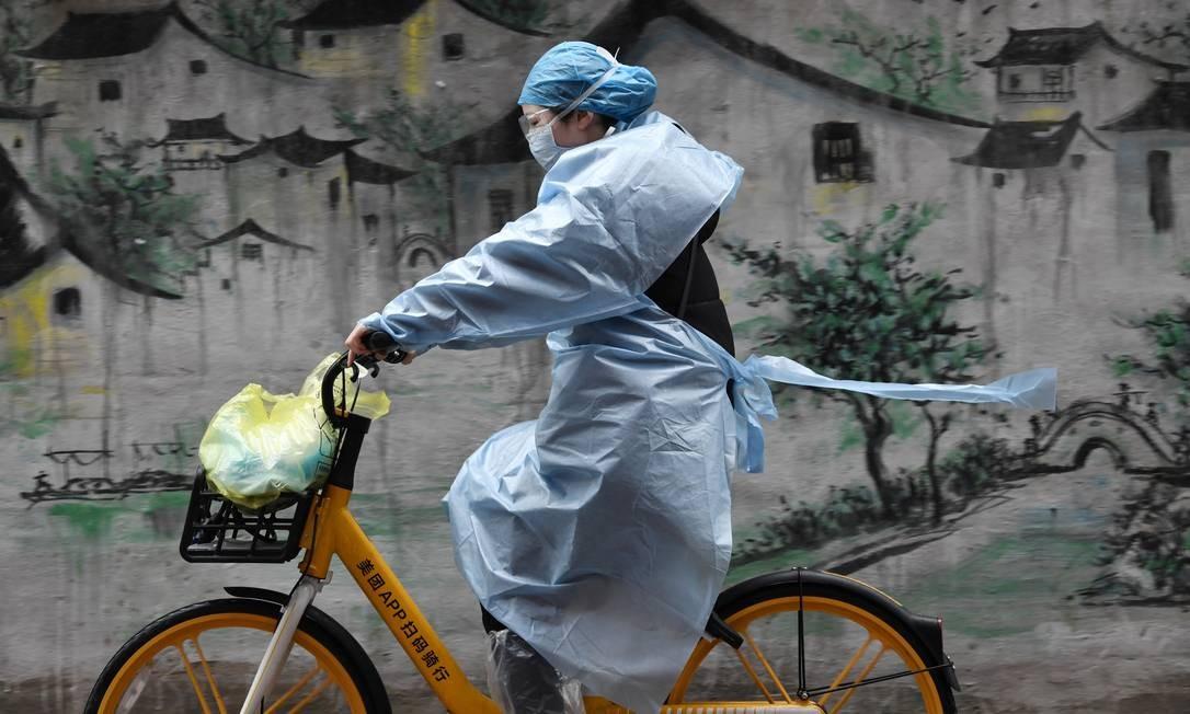 Mullher usando equipamento de proteção anda de bicicleta em Wuhan, cidade chinesa epicentro da epidemia Foto: STRINGER / REUTERS