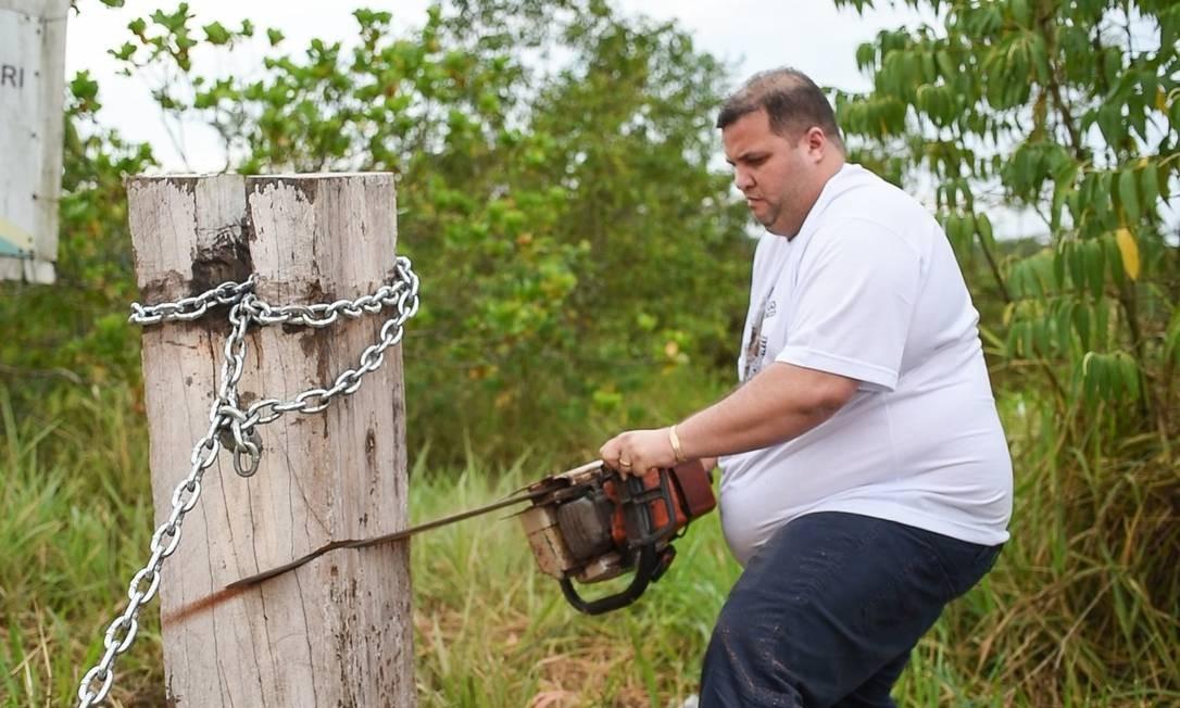 O deputado estadual Jeferson Alves (PTB-RR) serra o tronco e corta a corrente que bloqueava o acesso à BR-174, onde vivem os índios Kinja, na TI Waimiri-Atroari Foto: Divulgação