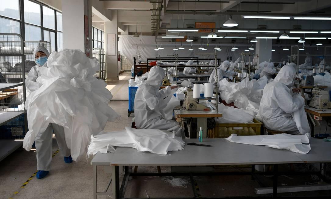 Operários de fábricas que voltaram a operar na China usam roupas especiais para evitar contaminação por Covid-19 Foto: Noel Celis / AFP