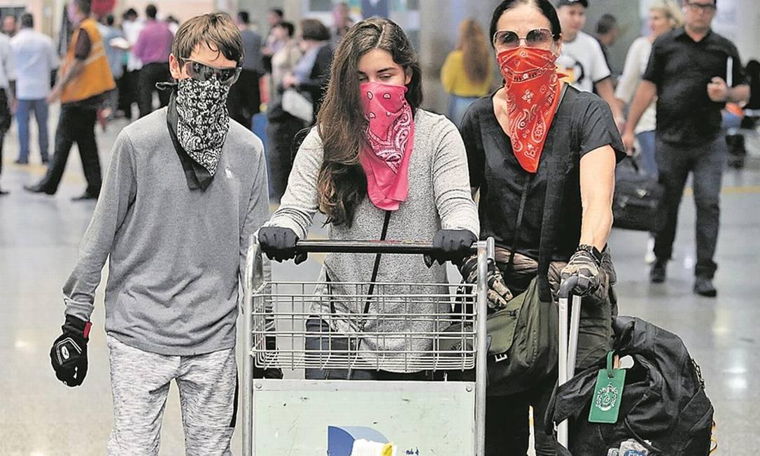 Desembarque de passageiros no Aeroporto Internacional do Galeão: máscaras improvisadas e luvas para evitar infecções Foto: FABIANO ROCHA/27-2-2020