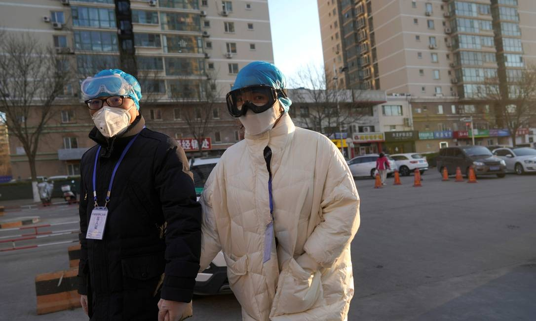 Em Pequim, pessoas usam tocas de plástico, óculos de proteção com máscaras contra o coronavírus Foto: STRINGER / REUTERS