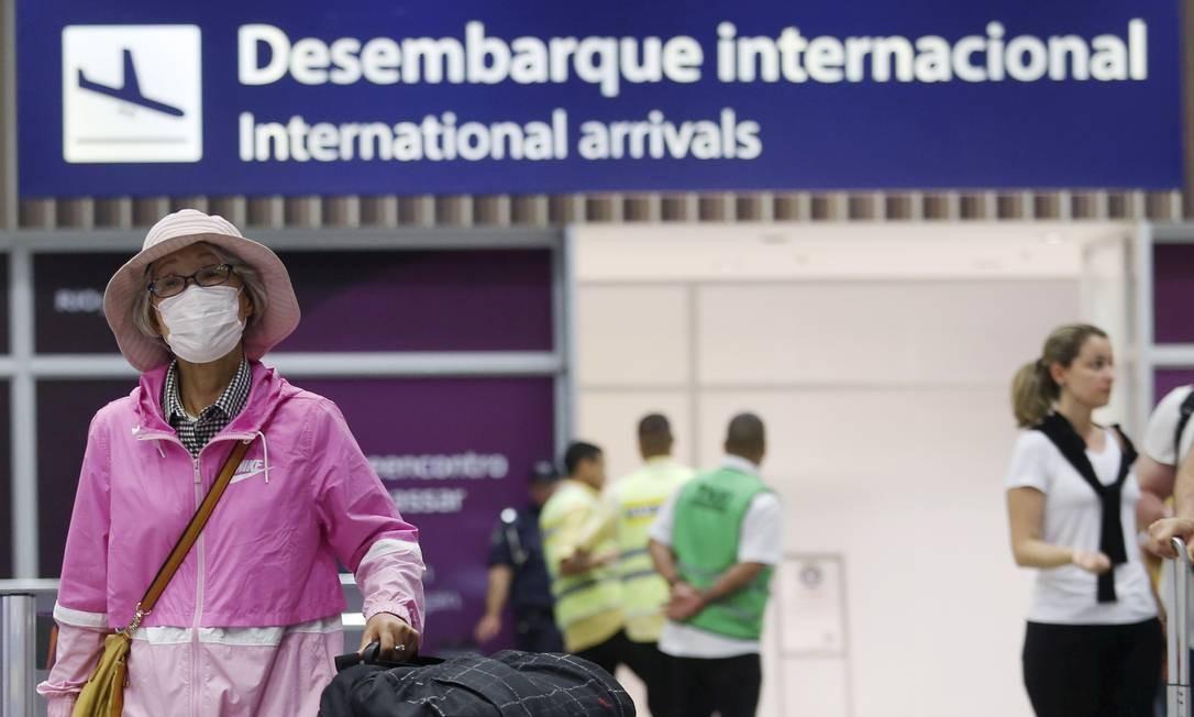 Passageiros desembarcam com máscaras no Aeroporto Internacional do Galeão Foto: FABIANO ROCHA / Agência O Globo