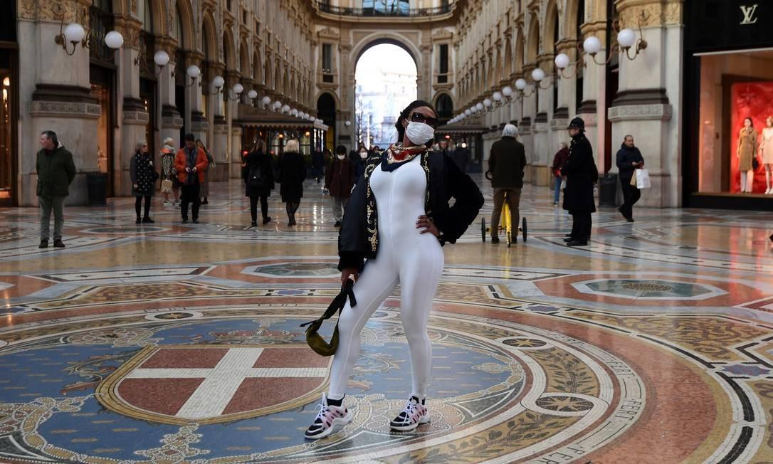 Lembrança de viagem com máscara: turista na famosa Galeria Vittorio Emanuele II, em Milão Foto: Miguel Medina/AFP / Miguel Medina/AFP
