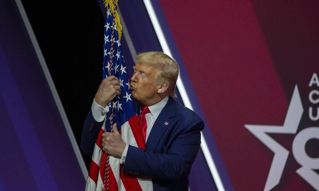 Trump abraça a bandeira americana durante discurso no encontro anual da Conferência de Ação Política Conservadora Foto: TASOS KATOPODIS / AFP