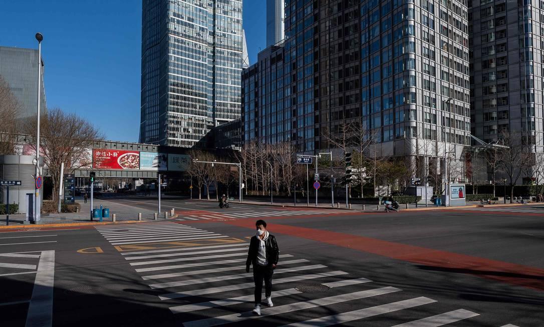 Homem com máscara de proteção contra o novo coronavírus atravessa rua em distrito financeiro deserto de Pequim, capital da China, nesta terça-feira (3) Foto: NICOLAS ASFOURI / AFP