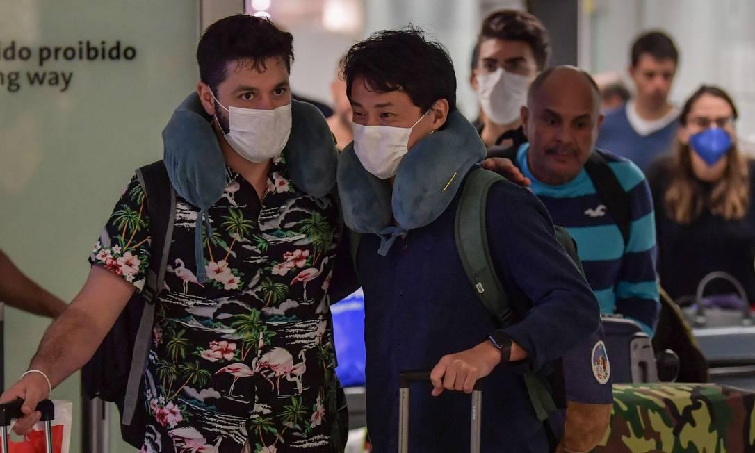 Passageiros da Itália usam máscaras ao desembarcar em Guarulhos (SP) Foto: NELSON ALMEIDA / AFP
