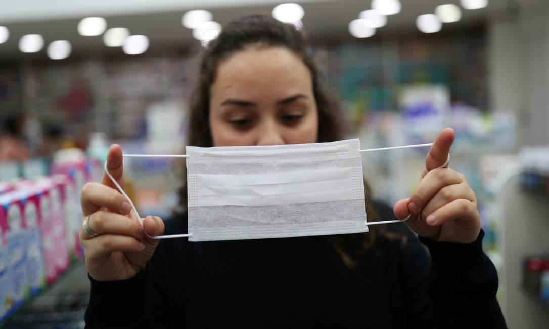 Vendedora mostra máscara de proteção, em Guarulhos (SP), usada diante da epidemia do novo coronavírus pelo mundo. O Brasil tem dois casos confirmados. Foto: AMANDA PEROBELLI / REUTERS