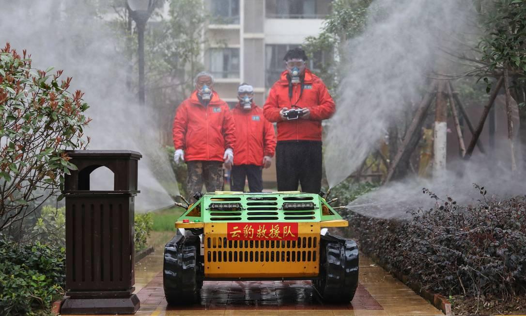 Voluntários usam um robô para espalhar desinfetante em área residencial de Wuhan, na China, o epicentro da epidemia do novo coronavírus Foto: STR / AFP