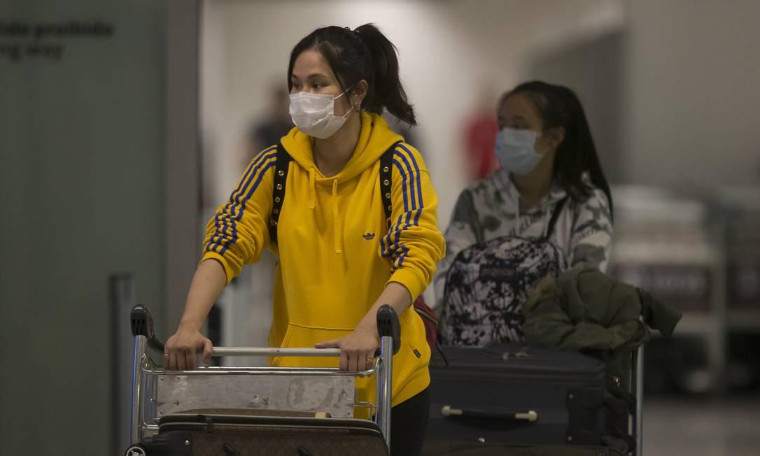 Passsageiras vindo de países asiaticos desembarcam com máscaras no Aeroporto Internacional de Guarulhos, em São Paulo Foto: Edilson Dantas / Agência O Globo