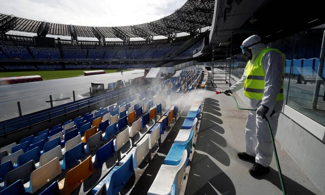 Funcionário higieniza estádio de San Paolo, em Nápoles, na Itália, que sediaria a semifinal da Copa Itália, entre Napoli e Inter de Milão. A partida foi adiada como medida para conter o coronavírus. Foto: CIRO DE LUCA / REUTERS