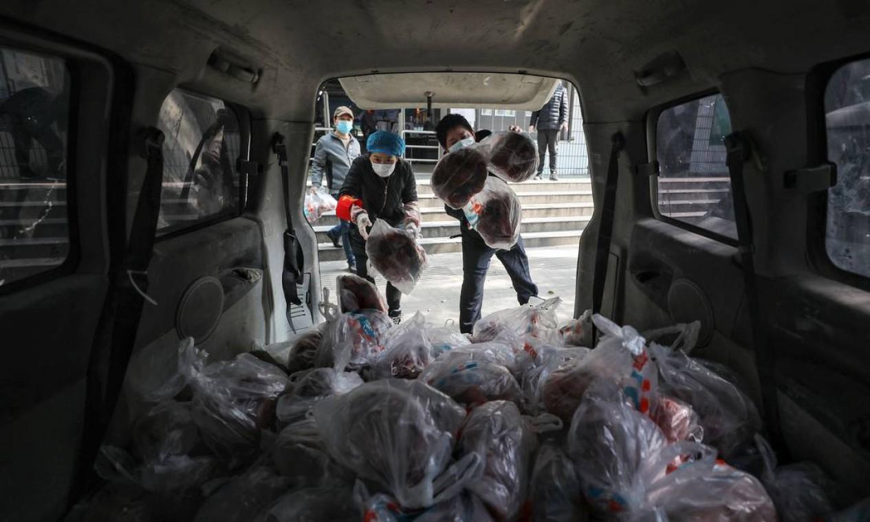 Supermercados de Wuhan, considerado o epicentro da epidemia da COVID-19, entregam vegetais ensacados para os moradores Foto: STR / AFP