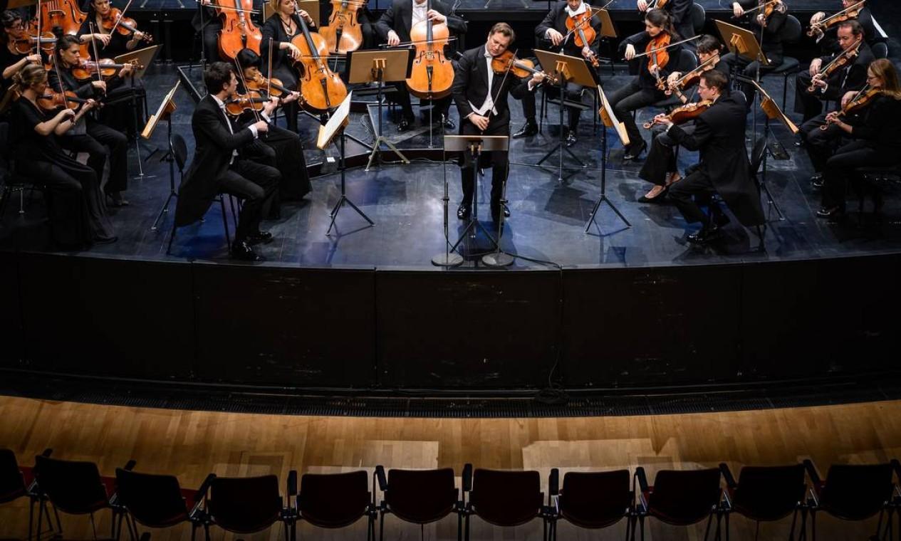 O violinista francês Renaud Capucon (centro) toca peças de Beethoven, Schubert e Mozart com a Orquestra de Câmara de Lausanne durante um concerto a portas fechadas devido ao novo coronavírus. As apresentações serão transmitidas pelo rádio e televisão pública suíça RTS Foto: Fabrice Coffrini / AFP