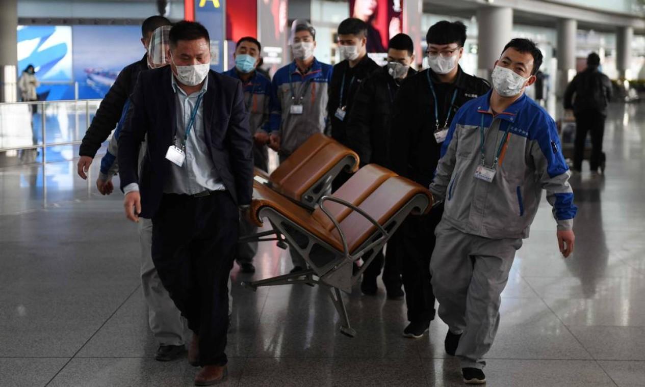 Trabalhadores usam máscaras ao remover assentos de uma área pública no Aeroporto da Capital de Pequim. Nesta quinta, a China registrou mais 31 mortes pela nova epidemia da COVID-19 Foto: Greg Baker / AFP