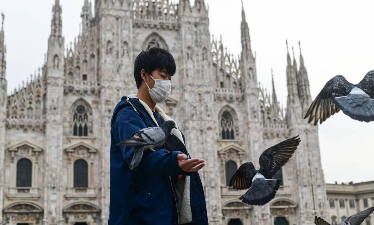 Um turista usando uma máscara respiratória dá comida a pombos na Piazza Duomo de Milão, nesta quinta-feira. A Itália fechou todas as escolas e universidades até 15 de março para ajudar a combater a propagação do coronavírus. A decisão do governo foi anunciada momentos depois que as autoridades de saúde disseram que o número de mortes do COVID-19 saltou para 107 e o número de casos passou de 3 mil Foto: Piero Cruciatti / AFP