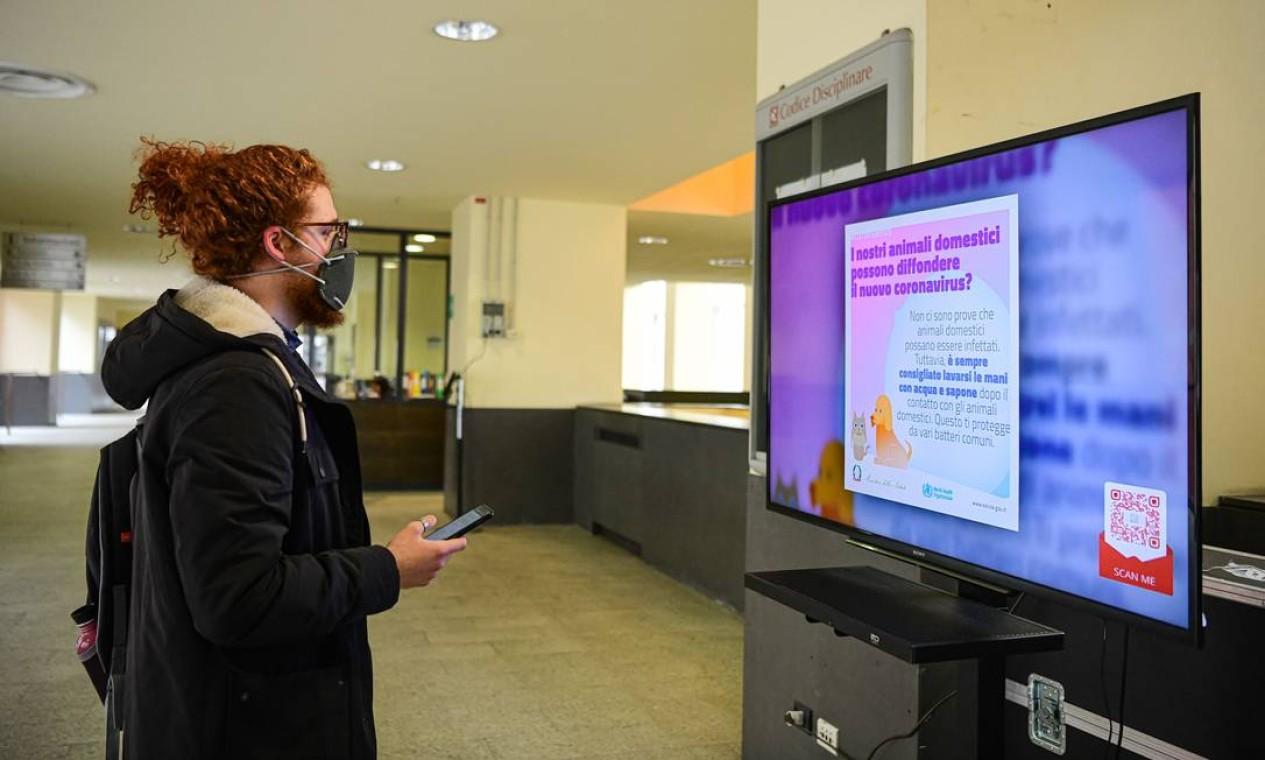 Estudante lê um aviso sobre o Coronavírus na Universidade Milano Bicocca, em Milão, Itália Foto: Piero Cruciatti / AFP