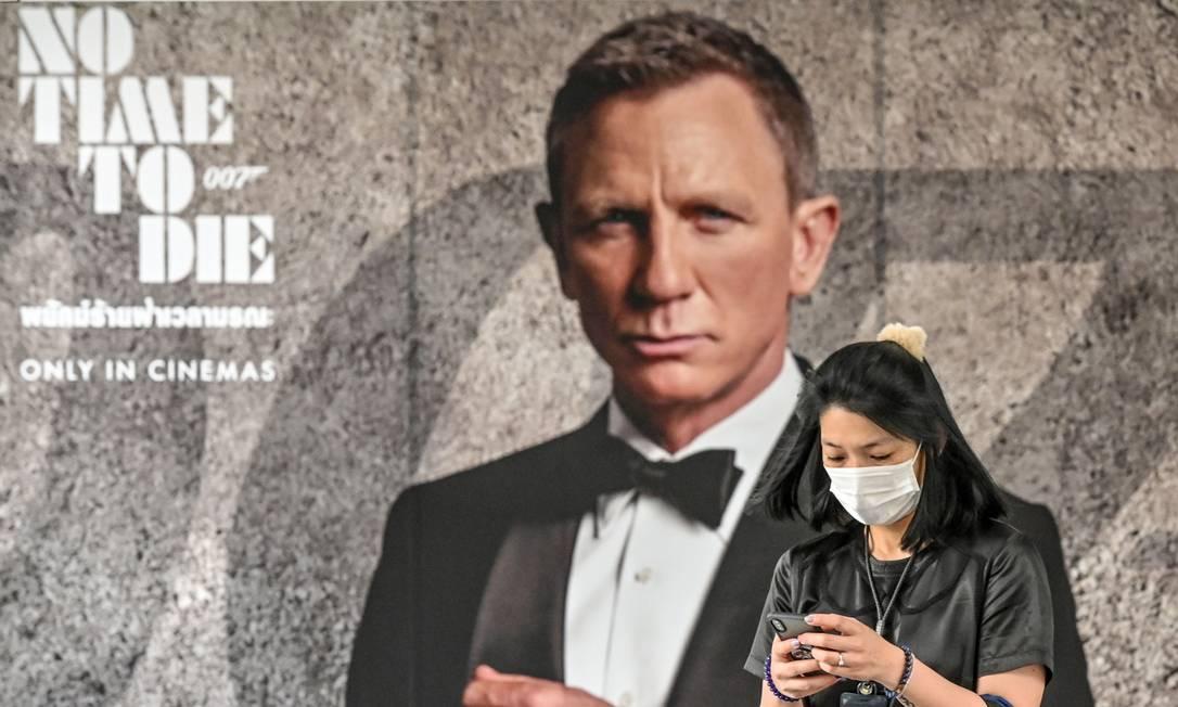 """Mulher circula com máscara em frente a cartaz do novo 007, """"Sem tempo para morrer"""" em Bangkok: longa foi o primeiro grande lançamento a ser adiado por conta do coronavírus Foto: MLADEN ANTONOV / AFP"""