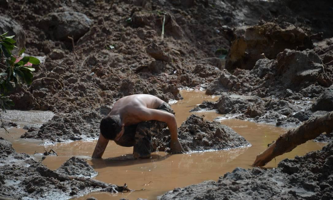 Um homem participa da busca de vítimas de um deslizamento de terra causado por chuvas torrenciais durante o final de semana, na favela Morro do Macaco Molhado, no Guarujá, São Paulo. Mais de 20 pessoas foram mortas pelas chuvas Foto: NELSON ALMEIDA / AFP