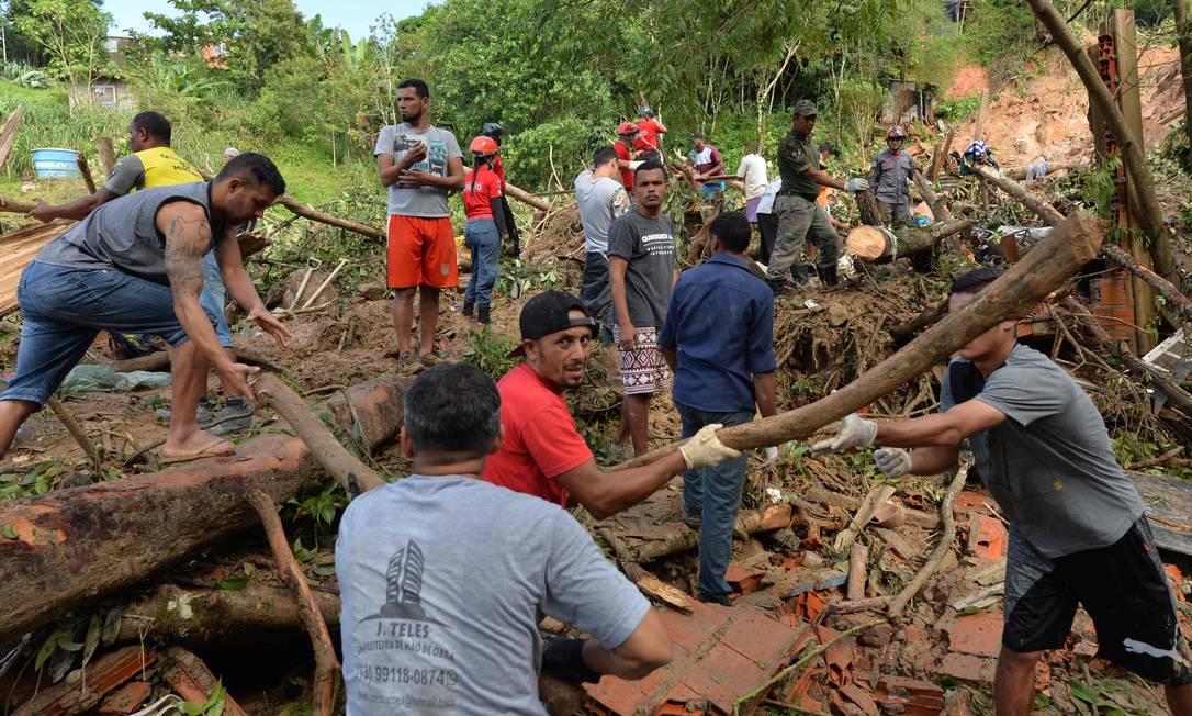 Moradores se juntam a equipes de resgate em busca de vítimas de um deslizamento de terra causado por chuvas torrenciais durante o final de semana, no Morro do Macaco Molhado, no Guarujá, São Paulo Foto: NELSON ALMEIDA / AFP