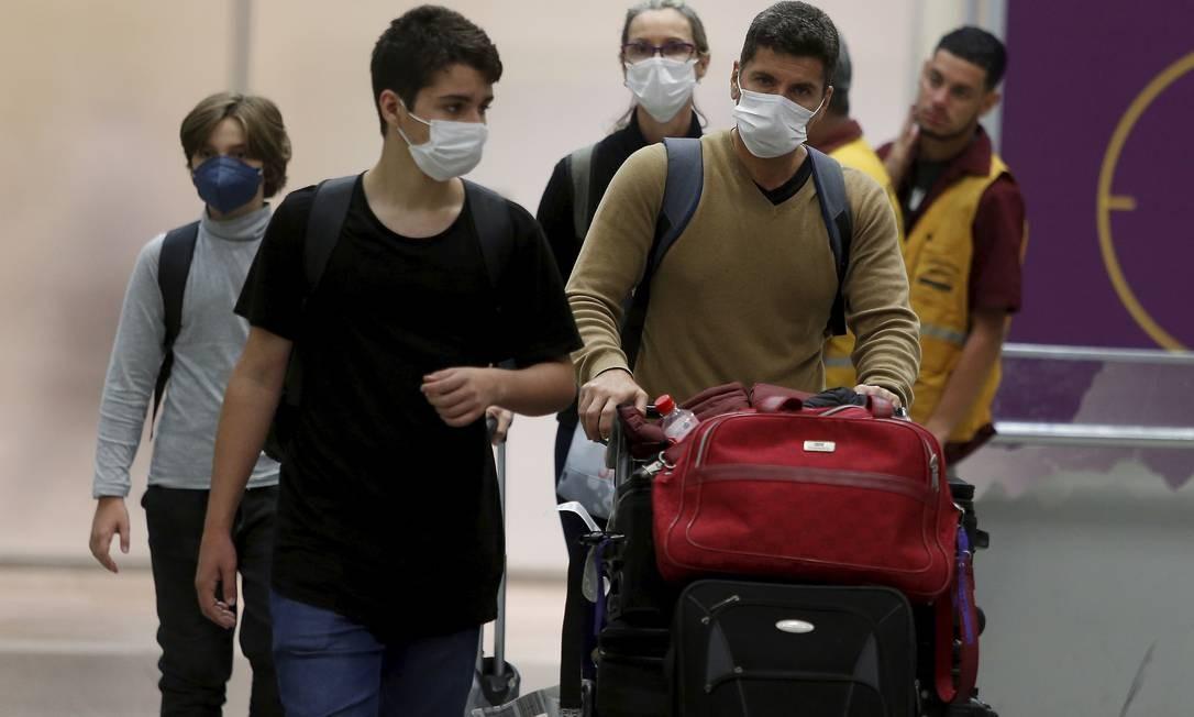 Turistas e brasileiros desembarcam com máscaras cirúrgicas no Aeroporto Internacional do Galeão. Foto: FABIANO ROCHA / Agência O Globo
