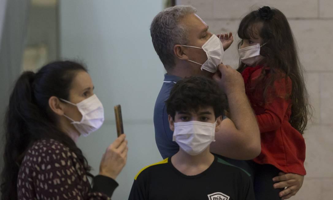 Família desembarca com máscaras protetoras no Aeroporto de Guarulhos, em São Paulo Foto: Edilson Dantas / Agência O Globo