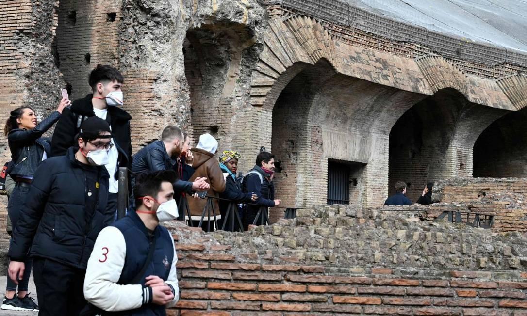 Turistas usam máscaras enquanto visitam o Coliseu, em Roma Foto: TIZIANA FABI / AFP