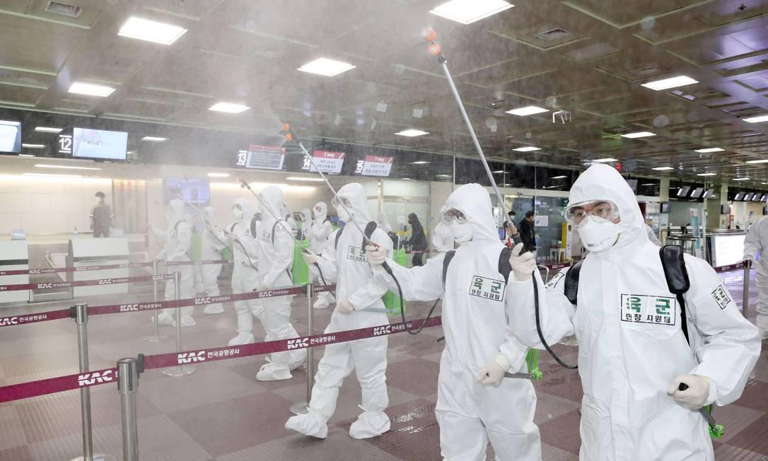 Soldados sul-coreanos usam desinfetante de spray de ajudar a impedir a propagação do coronavírus Covid-19, no Aeroporto Internacional de Daegu em Daegu, nesta sexta-feira. País é o maior foco do novo coronavírus, com quase 7 mil infectados, de acordo com Centros de Controle e Prevenção de Doenças Foto: - / AFP