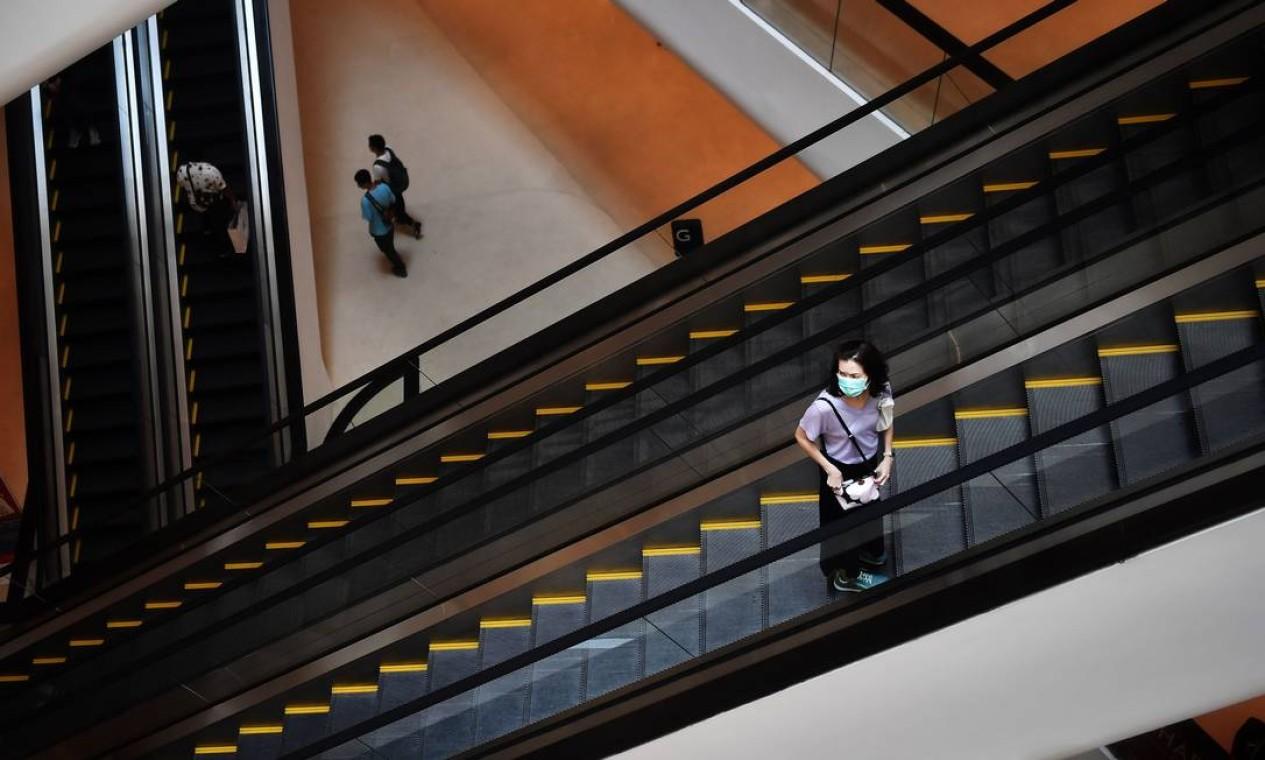 Mulher usando máscara de proteção anda aparece sozinha em um dos principais shoppings de Bangcoc, nesta sexta. Tailândia registrou a primeira morte em decorrência da Covid-19 neste mês Foto: Lillian Suwanrumpha / AFP