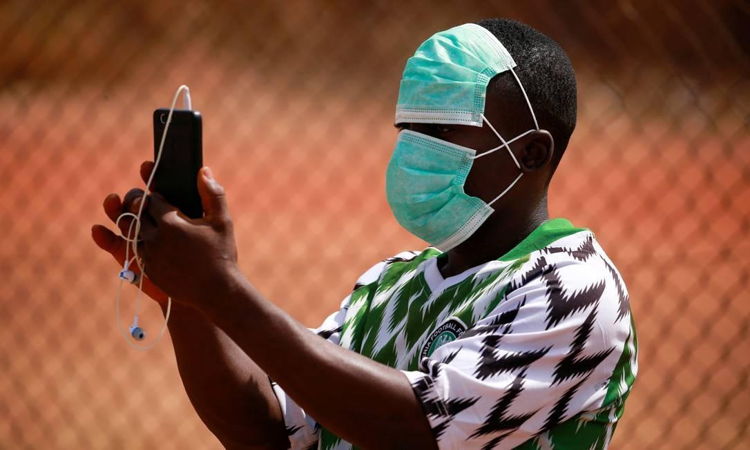 Garoto nigeriano é fotografado usando duas máscaras de proteção durante uma partida amistosa de futebol para o Dia Internacional da Mulher em Abuja, Nigéria Foto: Afolabi Sotunde / Reuters