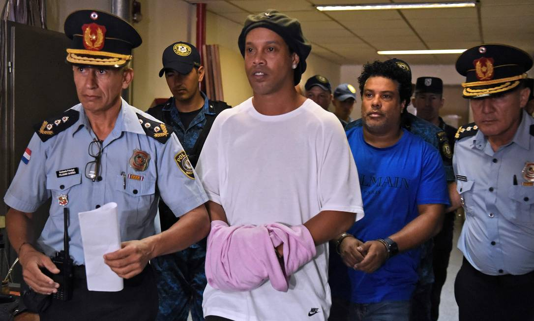 Ronaldinho e o irmão chegam algemados para prestar depoimento ao MP no Paraguai Foto: Norberto Duarte / AFP