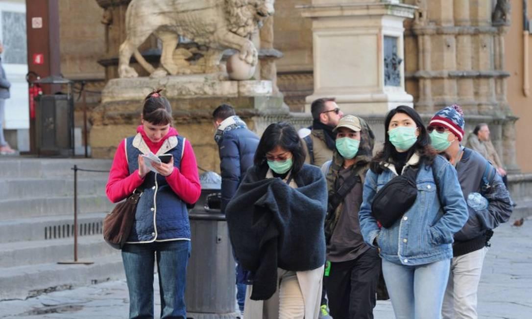 Turistas usam máscaras para se proteger enquanto caminham pelas ruas de Florença Foto: JENNIFER LORENZINI / REUTERS
