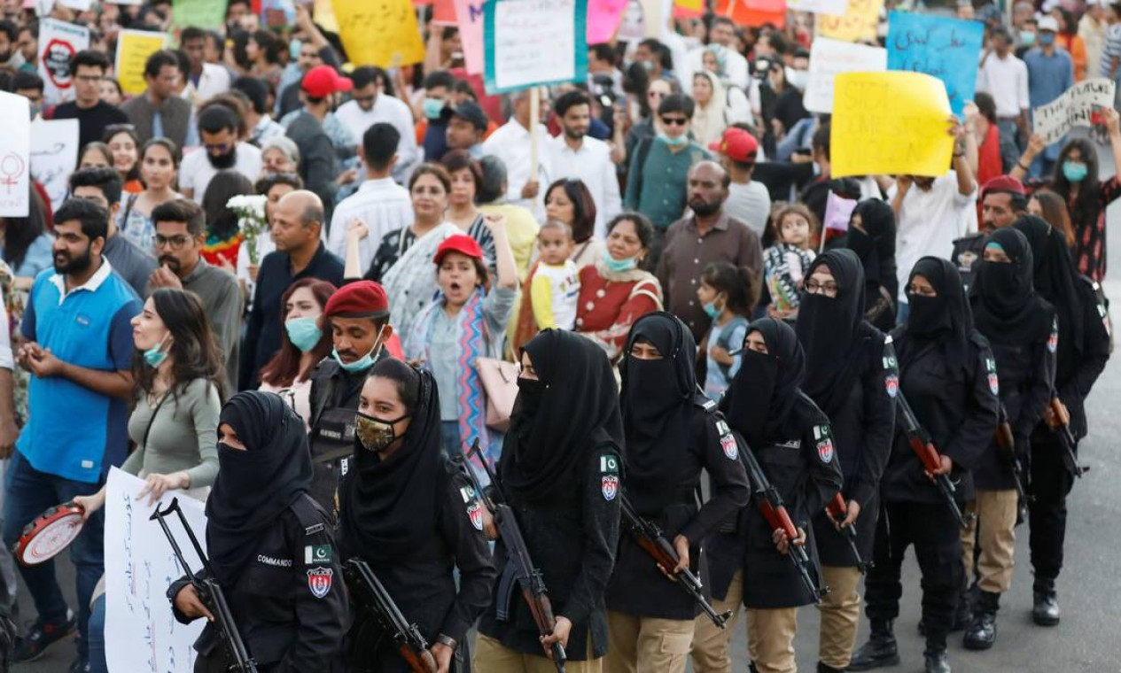 Policiais fazem cordão de segurança para proteger grupo que participava de marcha das mulheres em Karachi, no Paquistão. Manifestantes foram atacadas em outras cidades do país Foto: AKHTAR SOOMRO / REUTERS