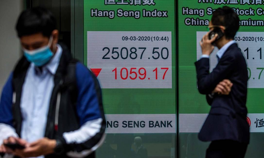 Painel eletrônico mostra índice da Bolsa de Hong Kong, que teve forte queda nesta segunda-feira Foto: Isaac Lawrence / AFP