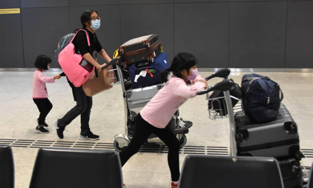 Passageiros vindos de Pequim desembarcam no Aeroporto Internacional de Guarulhos usando máscaras Foto: Fotoarena / Agência O Globo