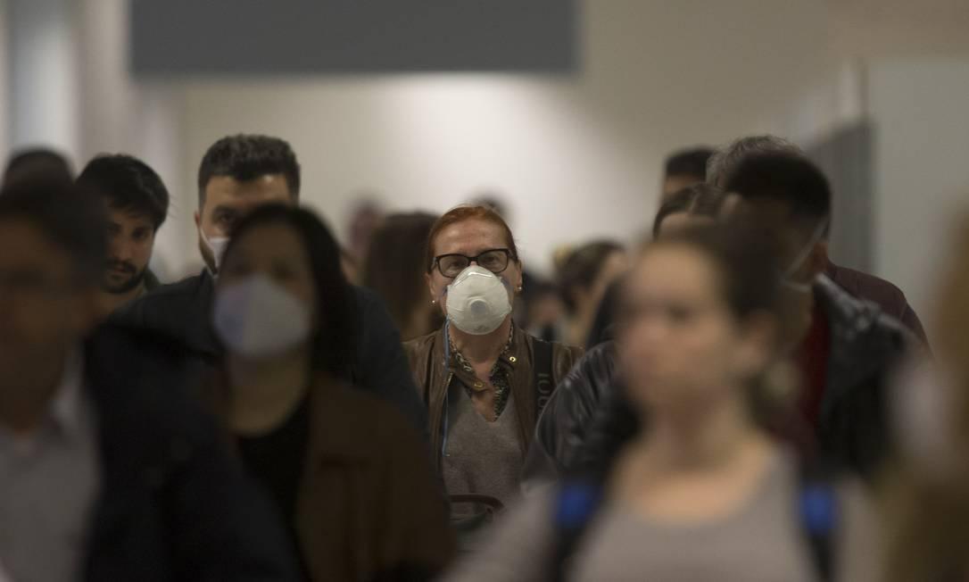 Passageiros usam máscaras no desembarque do aeroporto internacional de Guarulhos: medo de contaminação está levando a cancelamento de viagens Foto: Edilson Dantas/26-020-2020