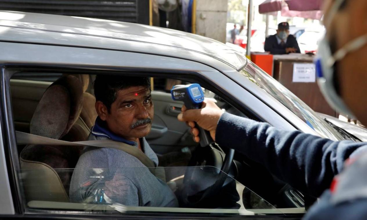Ameaça. Indiano tem aferida temperatura ao entrar em complexo empresarial em Nova Déli, Índia, nesta segunda Foto: Adnan Abidi / Reuters