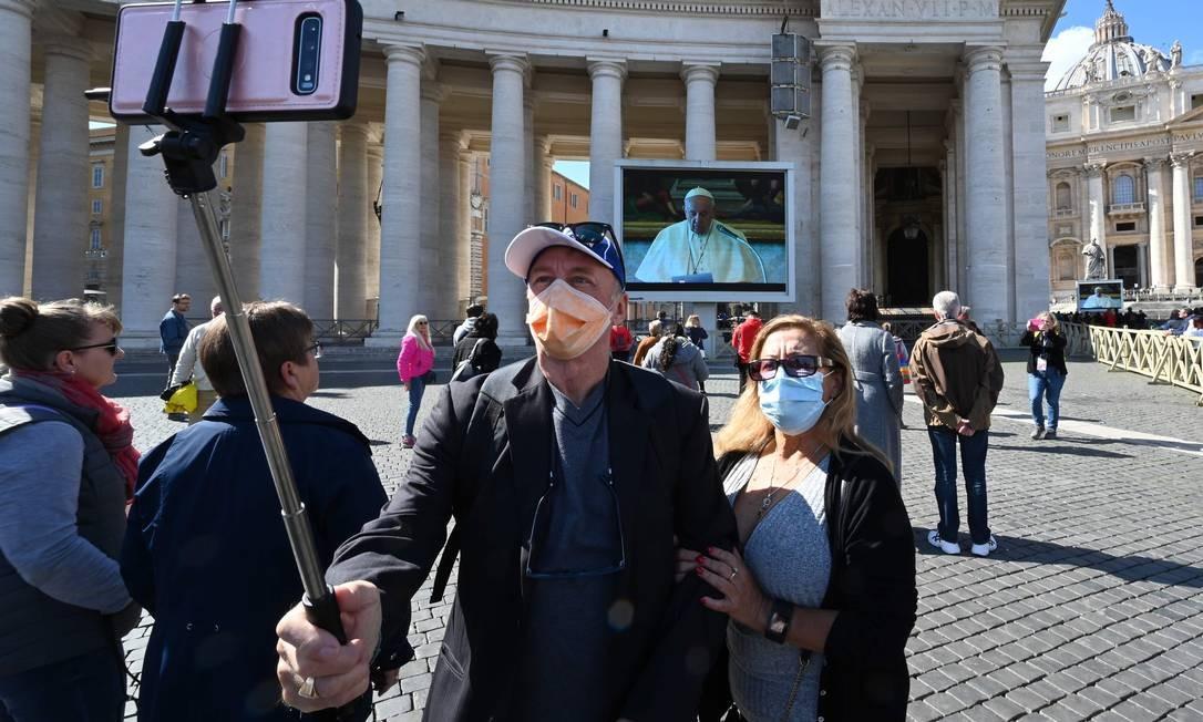 Casal tira selfie em frente a uma tela de transmissão ao vivo do Papa Francisco no domingo, na Praça de São Pedro, no Vaticano Foto: Alberto Pizzoli / AFP
