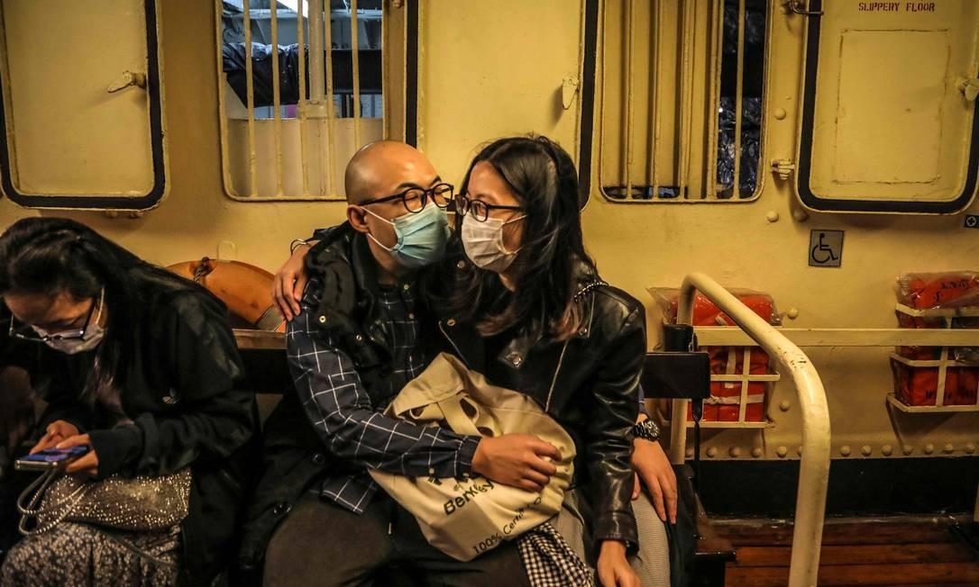 Tinha uma máscara no meio do caminho. Casal troca afeto em balsa que faz a travessia do porto de Victoria, em Hong Kong Foto: Vivek Prakash / AFP