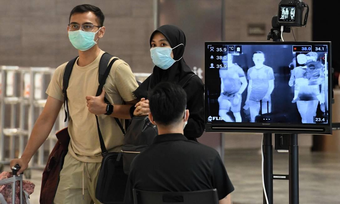 Um casal, usando máscaras protetoras, passa por verificação de temperatura no Aeroporto Internacional Changi, em Cingapura Foto: Roslan Rahman / AFP