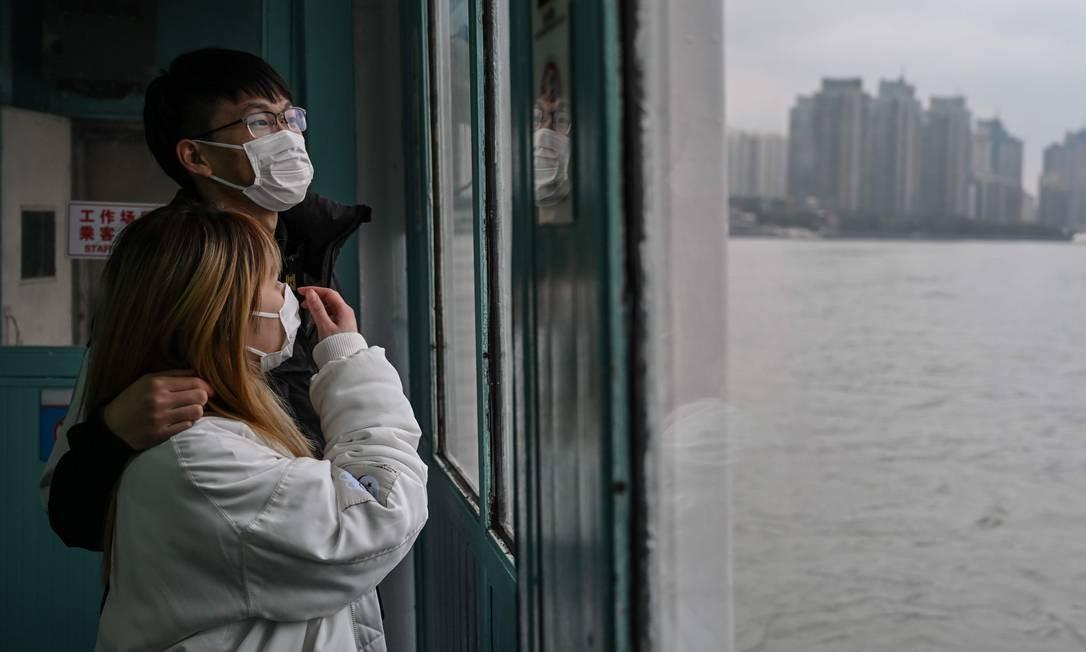 Casal olha através da janela de balsa que faz a travessia do rio Huangpu, em Xangai, China Foto: Hector Retamal / AFP