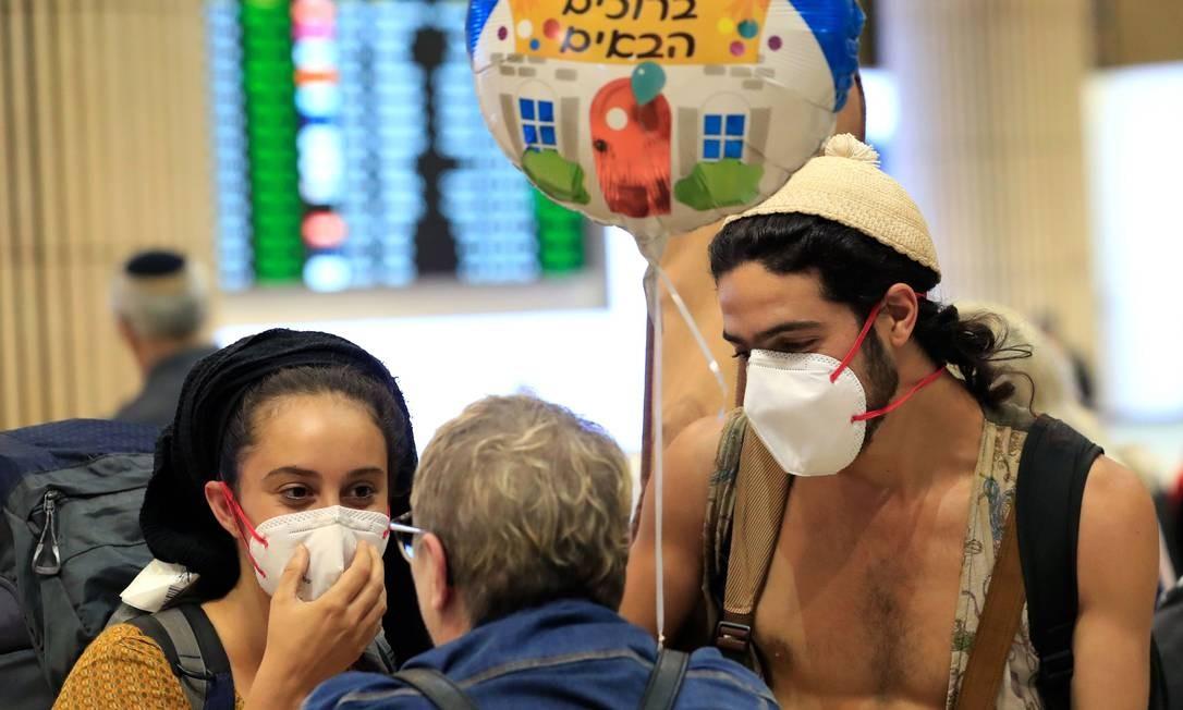 Jovem casal chega ao aeroporto Ben Gurion, em Tel Aviv, usando máscara de proteção. Israel ordenou uma quarentena de duas semanas às pessoas que chegassem da França, Alemanha, Espanha, Áustria e Suíça por causa de coronavírus Foto: Emmanuel Dunand / AFP
