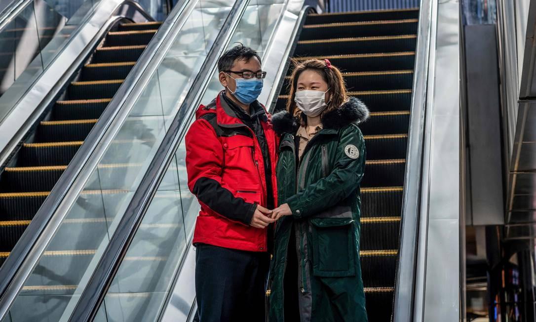 Casal usa máscara de proteção em escada rolante em um dos principais shoppings de Pequim, na China Foto: Nicolas Asfouri / AFP