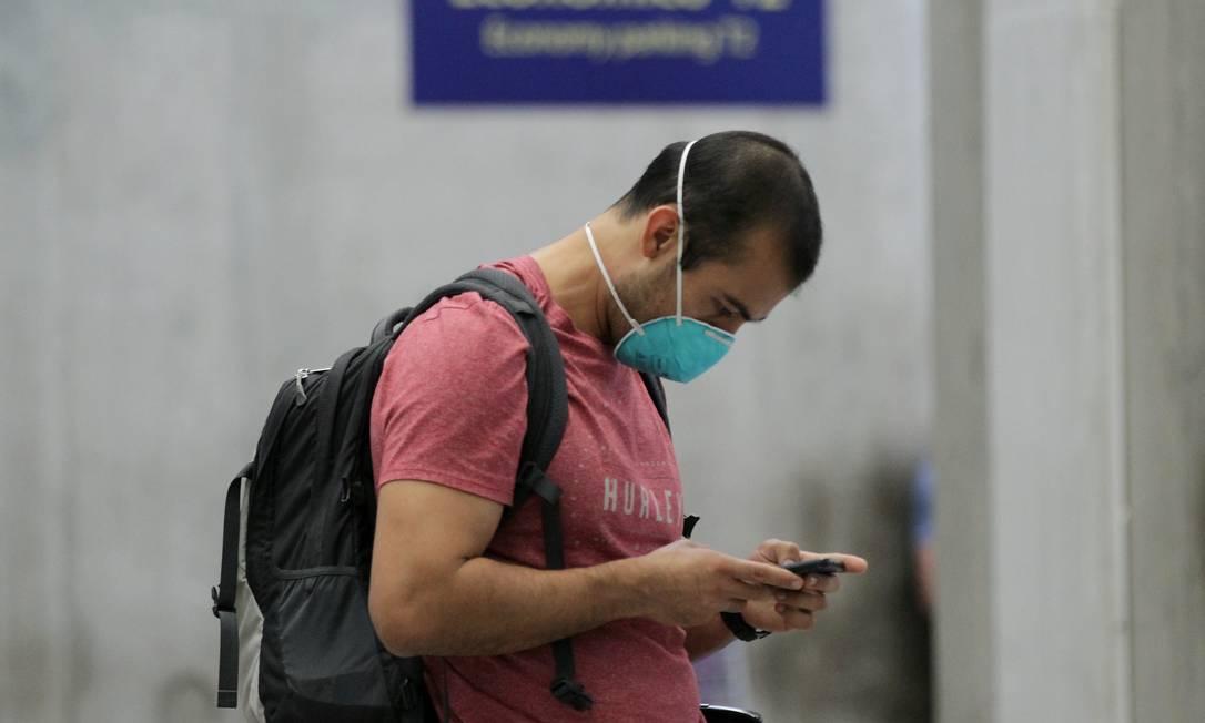 No aeroporto internacional do Rio, passageiros usam máscaras para se protegerem contra o coronavírus. Foto: GABRIEL DE PAIVA / Agência O Globo