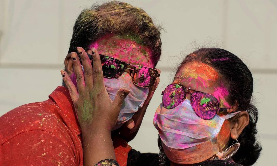 Casal participa do Holi em Hyderabad, na Índia, usando máscaras de proteção, por temor ao coronavírus Foto: Noah Seelam / AFP