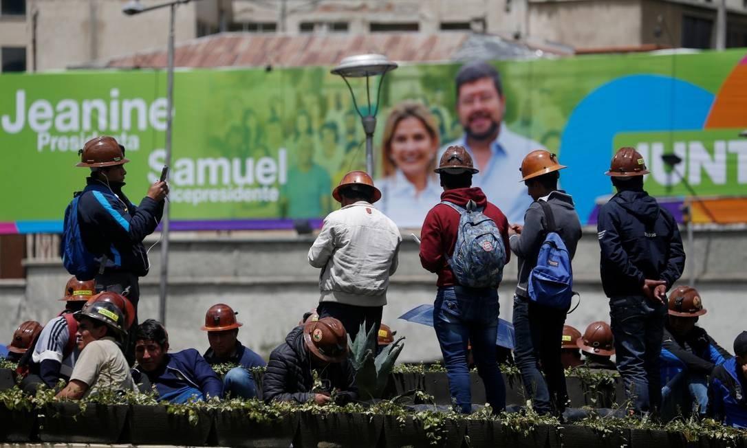 Mineiros diante de um cartaz de Áñez, em La Paz Foto: DAVID MERCADO / REUTERS