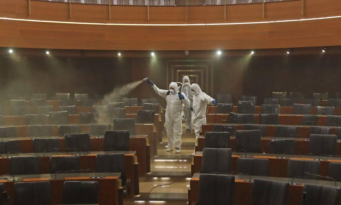 Agentes de saúde desinfetam mesas e cadeiras no Parlamento do Líbano, em Beirute; país registrou sua primeira morte por Covid-19 na última segunda-feira Foto: ANWAR AMRO / AFP