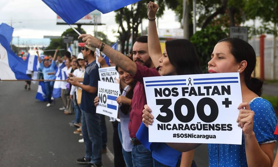 """Manifestantes fazem protesto antigoverno contra a violenta repressão do governo de Daniel Ortega; """"faltam-nos 300+ nicaraguenses"""", diz o cartaz Foto: MARVIN RECINOS / AFP / 14-07-2018"""