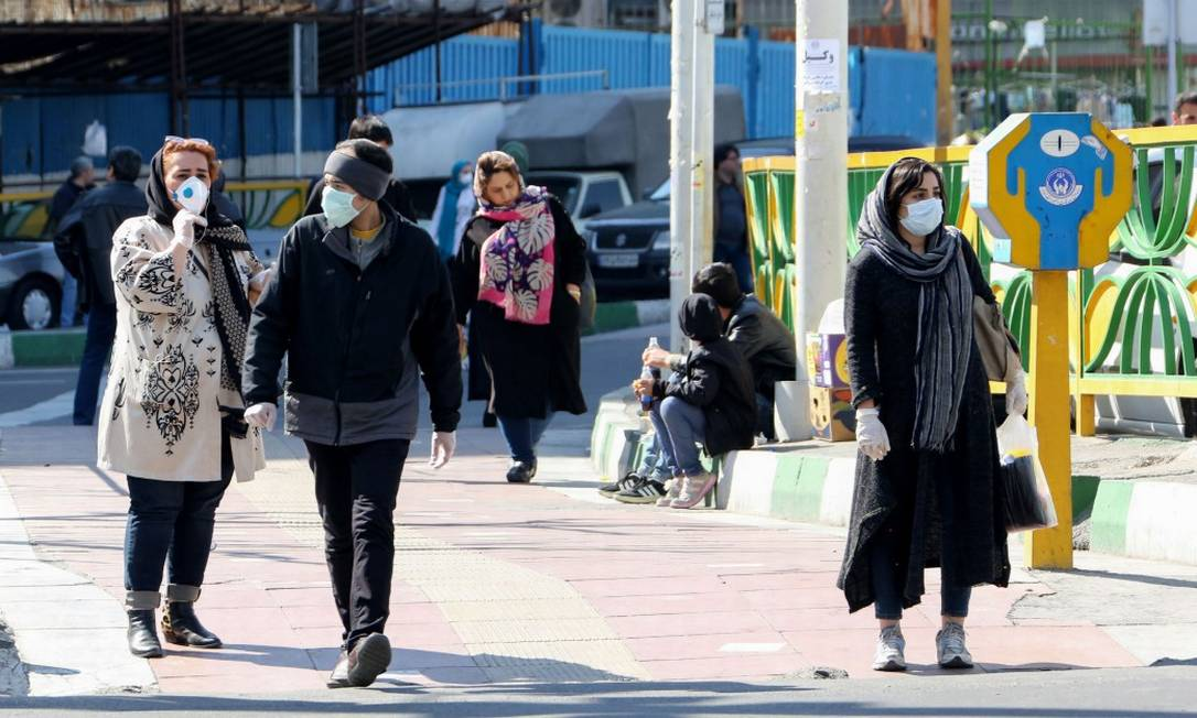 Iranianos caminham por Teerã usando máscaras Foto: ATTA KENARE / AFP