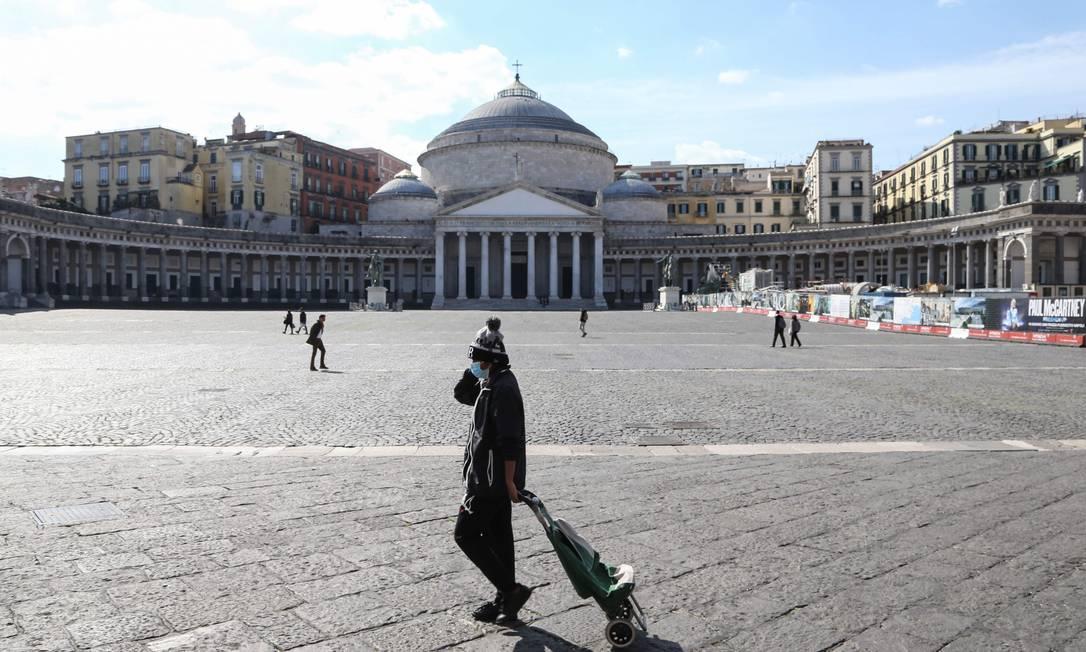 Pessoas caminham com máscaras de proteção na quase deserta Piazza del Plebiscito, em Nápoles, no Sul da Itália, no primeiro dia após a quarentena em todo o território italiano Foto: CARLO HERMANN / AFP
