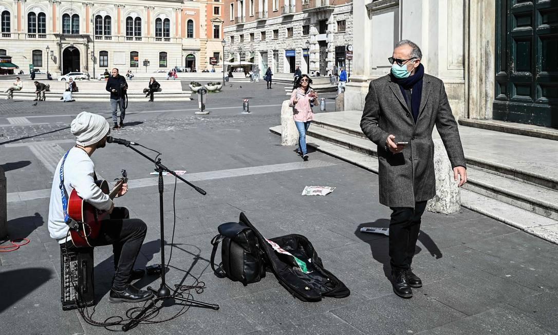 Homem usando máscara de proteção passa por um músico de rua na Piazza San Silvestro, no centro de Roma, nesta terça-feira. Ao fundo, pessoas sentadas mantém distância de segurança Foto: Vincenzo Pinto / AFP