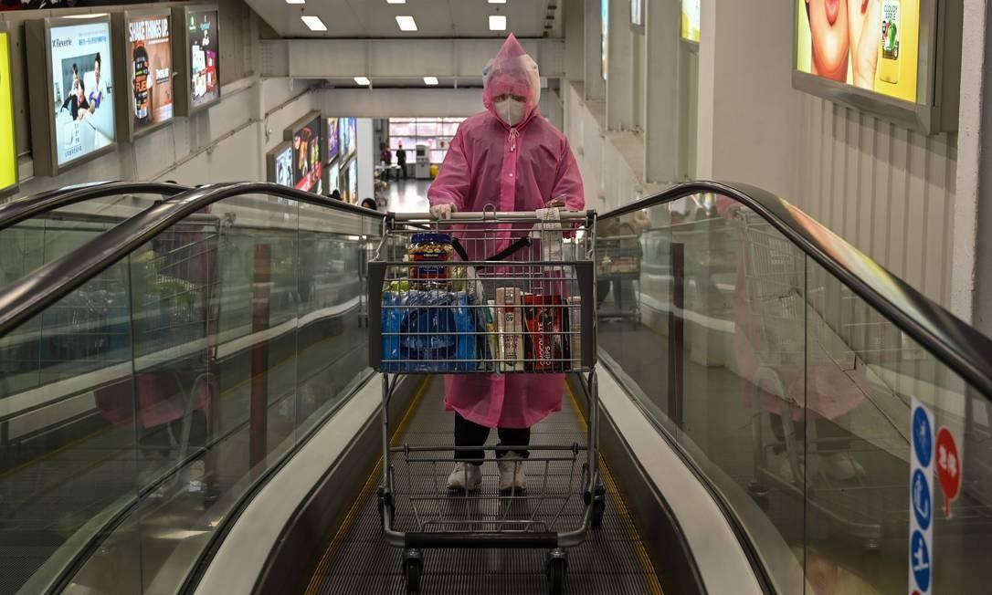Medidas extremas. Pessoa se protege com luva, calça, sapato fechado, capa e máscara para evitar contágio por coronavírus para ir a um mercado em Xangai, na China Foto: Hector Retamal / AFP